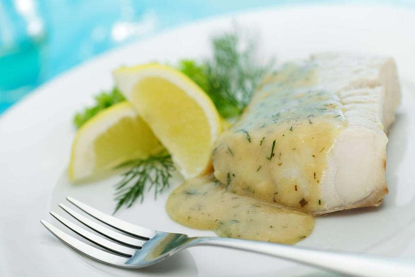 Ryba w sosie koperkowym z cytryną i świeżym koperkiem, na białym talerzu.