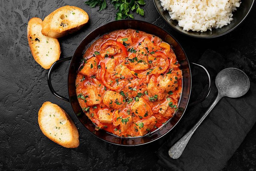 Ryba z warzywami w czarnym naczyniu, na czarnym blacie. Obok znajduje się pieczywo oraz ugotowany ryż.