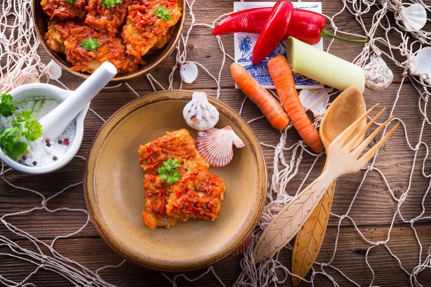 Klasyczna ryba po grecku w brązowej miseczce z muszelkami. Na stole leży sieć, drewniane sztućce i surowe warzywa.