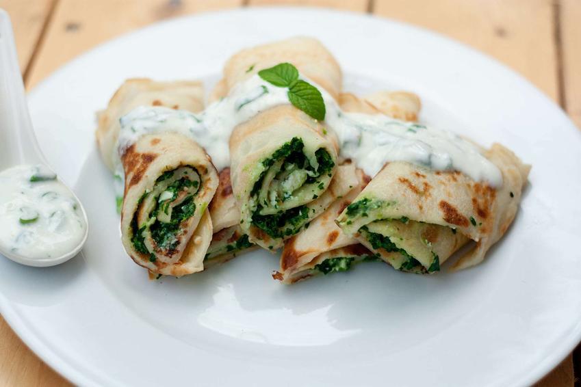 Naleśniki ze szpinakiem i twarogiem ułożone na białym talerzu, polane jogurtowym sosem, udekorowane zielonymi listkami.