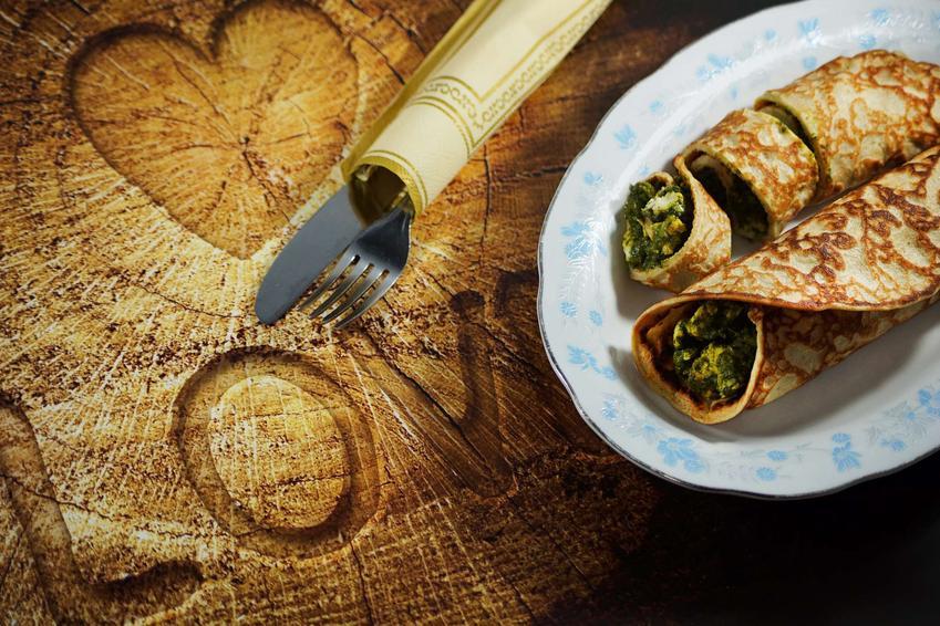 Naleśniki ze szpinakiem i pieczarkami ułożone na białym półmisku w niebieskie wzory, na drewnianym stole. Obok zestaw ozdobnych sztućców.