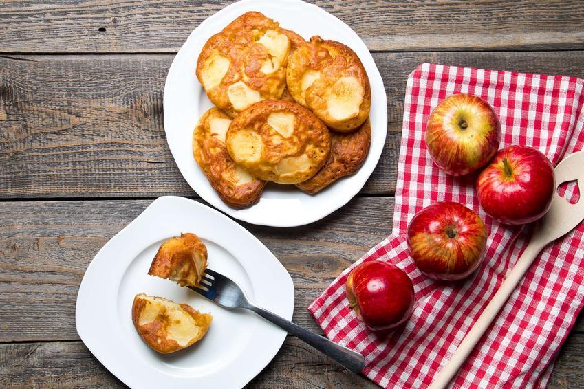 Racuchy z jabłkami ułożone na dwóch białych talerzach. Obok duże czerwone jabłka ułożone na ściereczce biało-czerwonej.