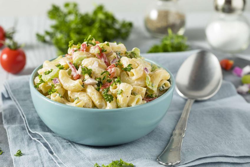 Sałatka makaronowa z warzywami podana w eleganckiej niebieskiej misce. Całość udekorowana posiekaną natką pietruszki.
