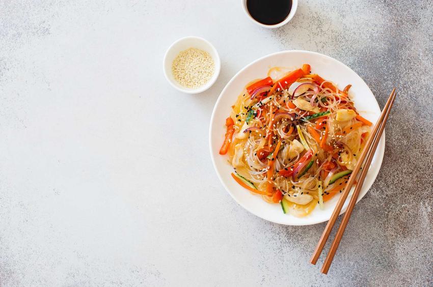 Sałatka z makaronem ryżowym i świeżymi warzywami w stylu orientalnym. Podana na okrągłym talerzyku z pałeczkami i sosem sojowym.