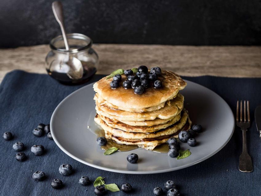 Protein pancakes są ułożone piętrowo na błękitnym talerzu. Na nich i obok porozkładane są borówki amerykańskie. Obok talerza stoi słoiczek z syropem klonowym.
