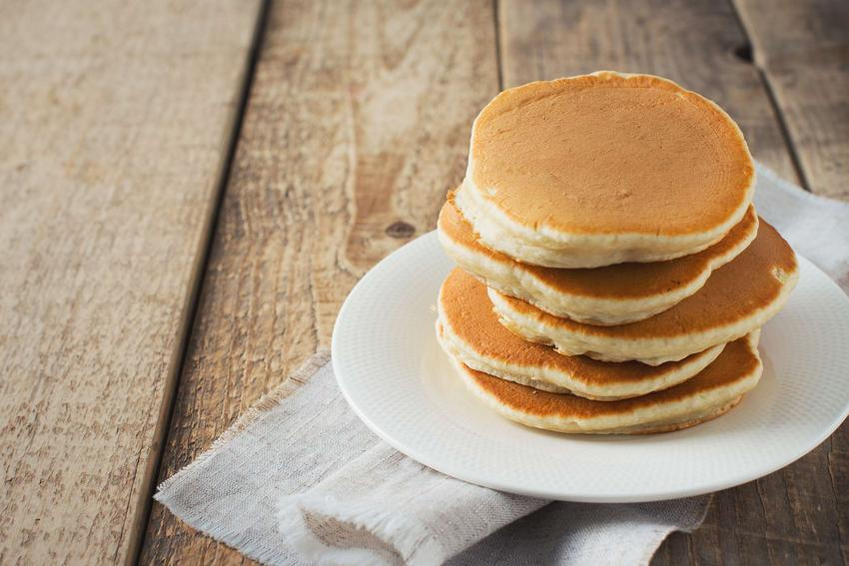 Pancakes na kefirze leżą na ceramicznym talerzyku.