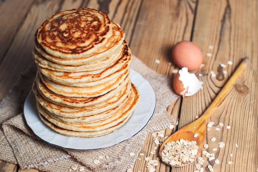 Placuszki z płatków owsianych i bananów znajdują się na białym talerzu. Obok leży drewniana łyżka pełna płatków owsianych oraz skorupka jajka.