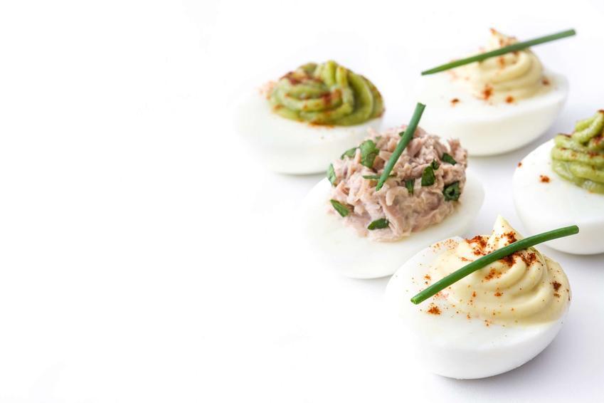 Na białym blacie ułożone są jajka z awokado. Jedno z nich ma farsz z awokado i tuńczyka, kolejne farsz z samego awokado oraz występuje jeszcze jajko z farszem tracycyjnym z żółtek. Wszystkie jajka udekorowane są szczypiorkiem.