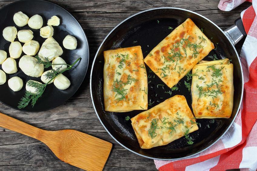 Naleśniki ze szpinakiem i mozzarellą podane na patelni, posypane koperkiem, obok miseczka z kulkami mozzarelli