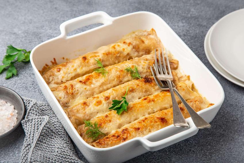 Naleśniki z mięsa mielonego podane w białej ceramicznej formie na szarym blacie, w tle dwa białe talerze