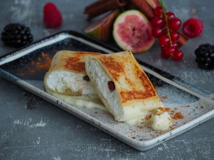 Naleśniki zapiekane z serem twarogowym ułożone są na prostokątnym talerzu. w oddali widać świeże owoce.