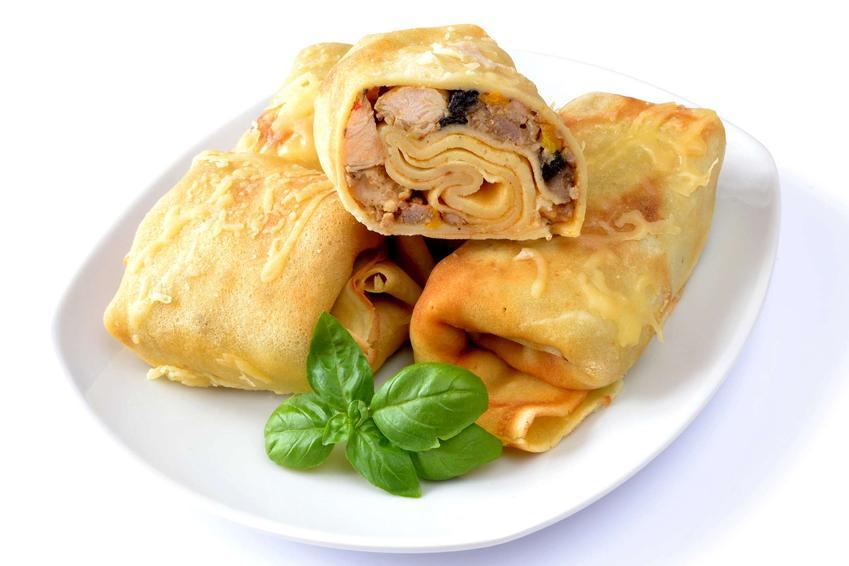 Naleśniki zapiekane z kurczakiem ułożone są na białym talerzu. Przyozdobione są zielonymi listkami bazylii.