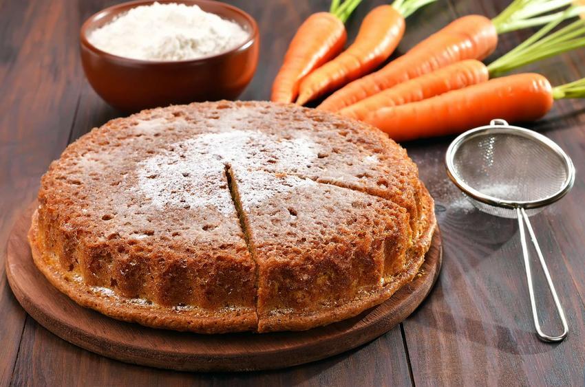 Na drewnianej paterze leży wegańskie ciasto marchewkowe. Jeden kawałek ciasta jest już ukrojony. Całość posypana jest cukrem pudrem. Patera znajduje się na drewnianym blacie, na którym leży jeszcze sitko z cukrem pudrem, świeże marchewki oraz miseczka.