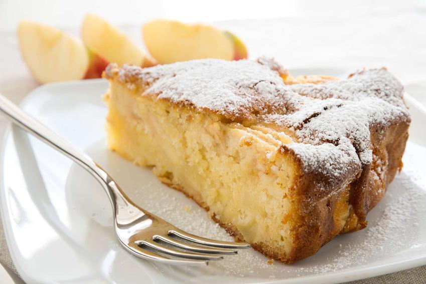 Kawałek ciasta z jabłkami, podany na talerzyku deserowym i posypany cukrem pudrem.