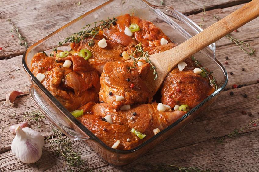 Marynata do karkówki wymieszana z mięsem podana w naczyniu żaroodpornym, przyozdobiona świeżym tymiankiem, na stole główka czosnku