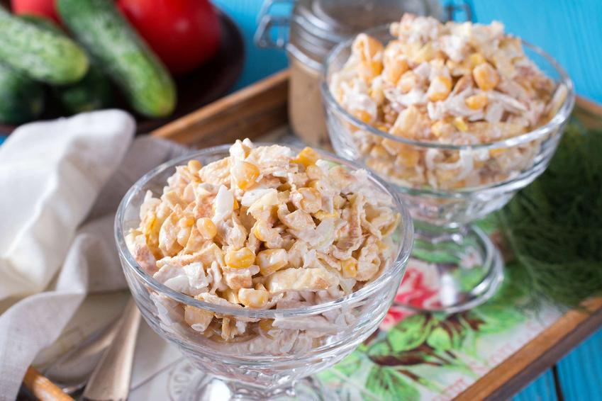 Sałatka z kurczakiem, ananasem, kukurydzą, jajkiem obtoczona w majonezie znajduje się w salaterkach. Salaterki umieszczone są na drewnianej desce.