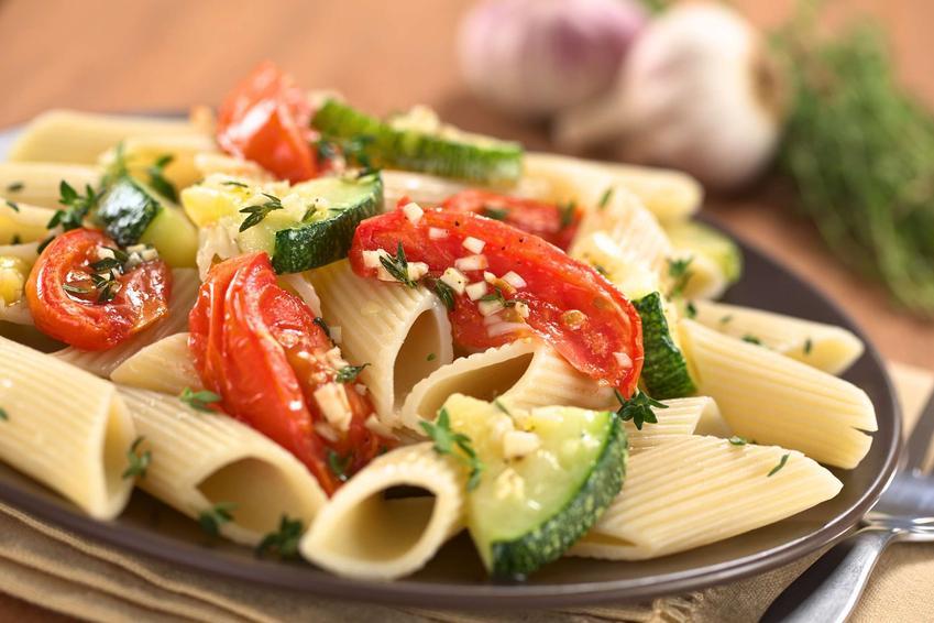 W talerzu znajduje się makaron z cukinią i pomidorami. W oddali na drewnianym blacie leżą dwie główki czosnku.