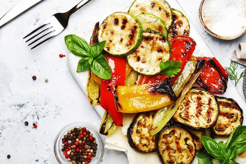 Warzywa na grilla znajdują się na białym talerzu. Obok leżą sztućce i stoi miseczka z ziarenkami pieprzu oraz miseczka z jasnym sosem.