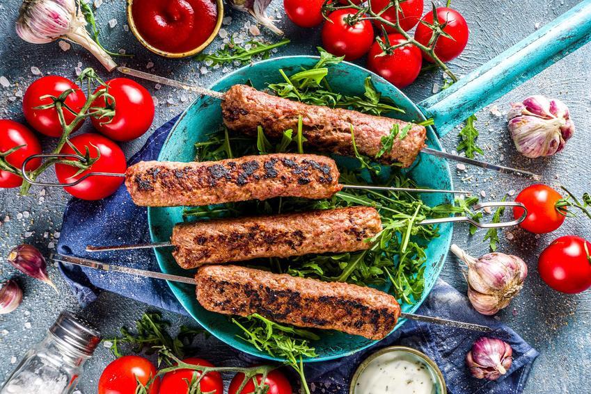 Mięso mielone z grilla podane w niebieskim rondelku, z rukolą, na około pomidorki na gałązkach, główki czosnku, sól i pieprz oraz dwa sosy w miseczkach