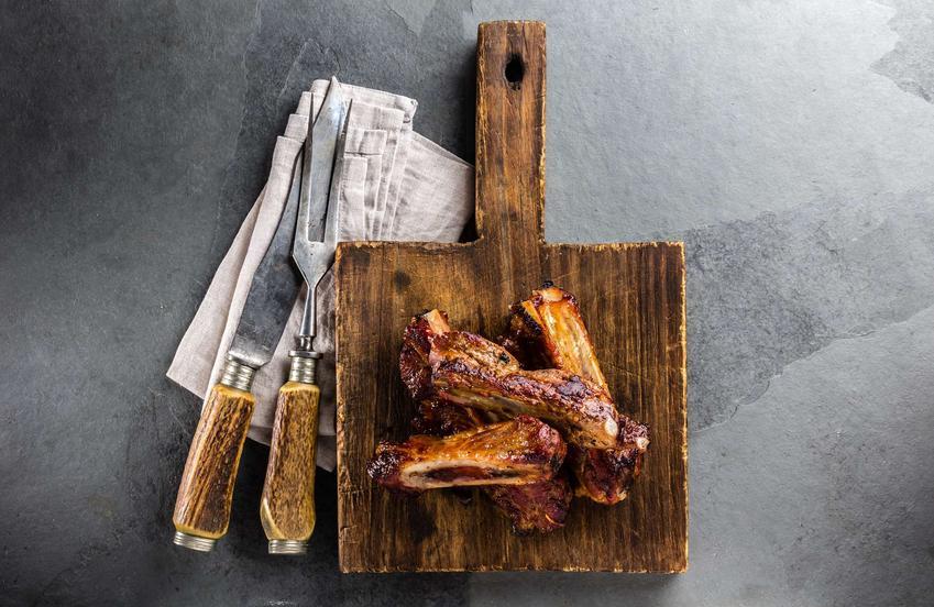 Żeberka w sosie własnym leżą na drewnianej desce. Obok na serwetce znajduje się nóż i widelec do mięsa.