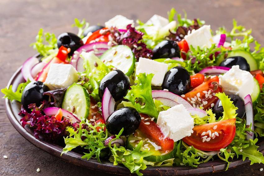 Sałatka na grilla z fetą, ogórkiem zielonym, pomidorkami koktajlowymi, czarnymi oliwkami, czerwoną cebulą, sałatą karbowaną i sezamem znajduje się w brązowym głębokim talerzu.