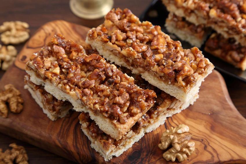 Ciasto snickers z prażonymi orzechami włoskimi. Kawałki ciasta ułożone dekoracyjnie na drewnianej desce.