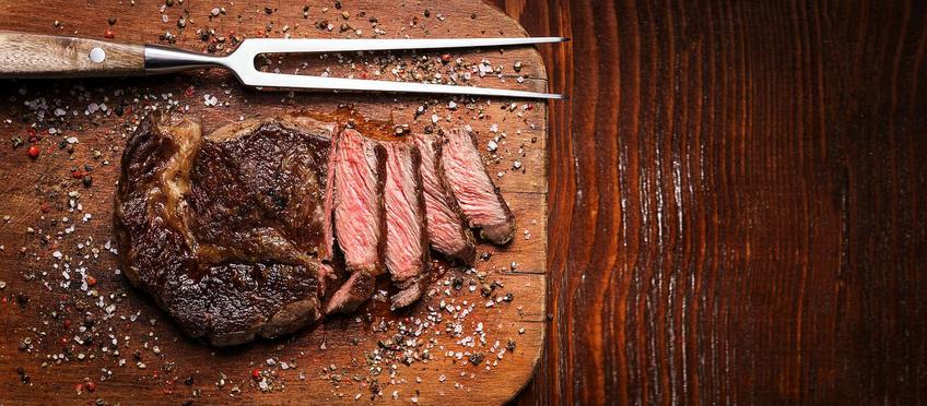 Pokrojony, średnio wysmażony stek wołowy z grilla na drewnianej desce.