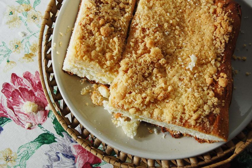 Ciasto drożdżowe z kruszonką, na białym talerzu w wiklinowym koszu leżącym na stole przykrytym obrusem w kwiaty.