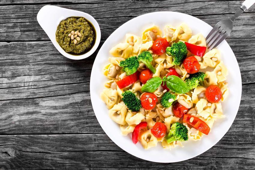Sałatka z tortellini, brokułami i pomidorkami koktajlowymi. Obok miseczka z zielonym sosem pesto.