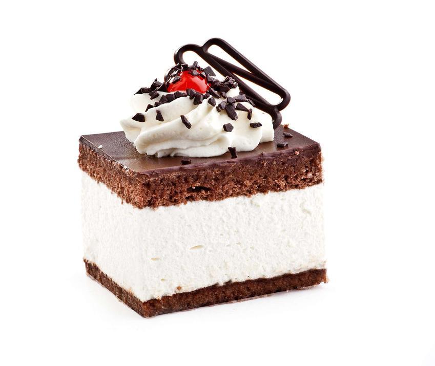 Ciasto wz ułożone jest na białym blacie z białym tłem. Udekorowane jest bitą śmietaną, wiśnią oraz obsypane potartą czekoladą.