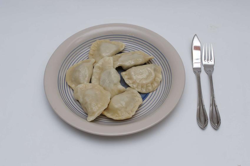 Gotowane pierożki ułożone na białym talerzu w niebieskie paski.