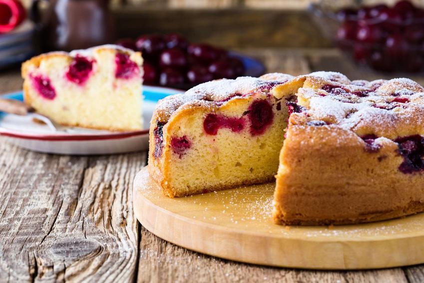 Ciasto z owocami znajduje się na drewnianej deseczce. Odkrojony kawałek ciasta leży na talerzu.