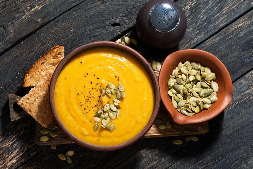 Zupa z dyni podana w małej miseczce udekorowana prażonymi pestkami dyni.