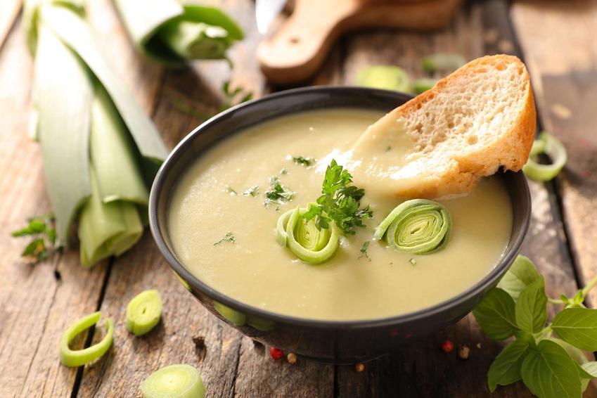 Zupa krem z porów podana w eleganckiej miseczce z pieczywem, udekorowana kawałkami pokrojonego pora.