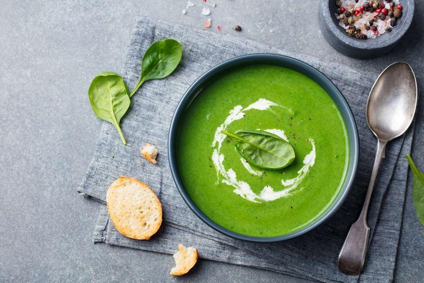 Zupa szpinakowa podana w eleganckiej miseczce i udekorowana kleksem z jogurtu.