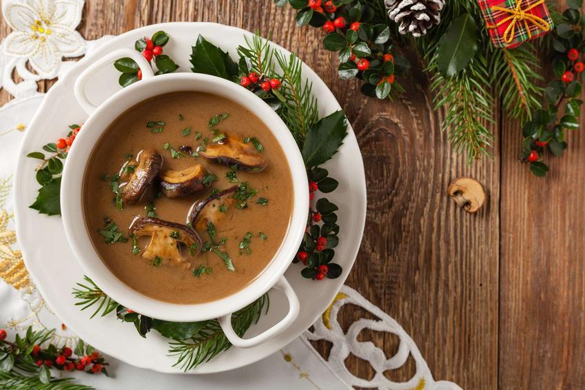 Zupa grzybowa na wigilię podana w bulionówce, otoczona świątecznymi dekoracjami.