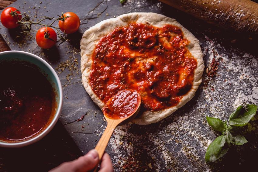 Fit pizza jest posmarowana sosem pomidorowym. Obok znajdują się pomidorki koktajlowe, sos pomidorowy w miseczce oraz liście świeżej bazylii.