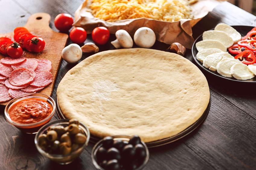 Spód do pizzy znajduje się na talerzu. Dookoła porozstawiane są składniki na pizzę: pieczarki, pomidory, ser mozzarella, salami, oliwki, starty ser, papryka i sos pomidorowy.