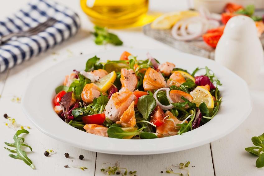 Sałatka z łososia pieczonego znajduje się w misce stojącej na białym blacie. W oddali widać pojemnik z oliwą z oliwek, ręcznik kuchenny, widelec, oraz pokrojone warzywa.