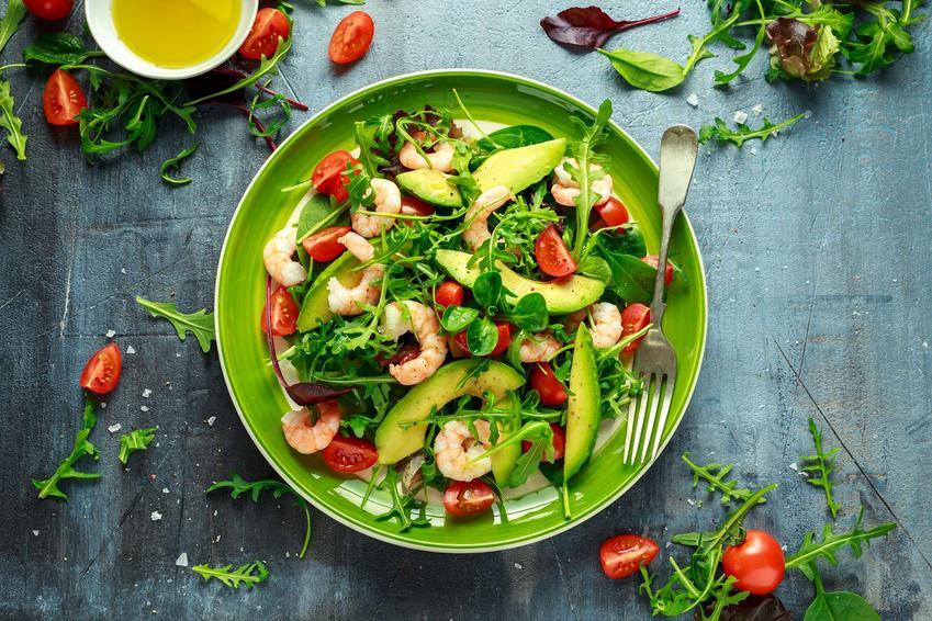 Na ciemnym blacie na zielonym talerzu leży sałatka z krewetkami, awokado i pomidorkami koktajlowymi. Dookoła talerza położone są liście rukoli, pomidorki koktajlowe oraz miseczka z sosem. Na talerzu obok sałatki położony jest widelec.