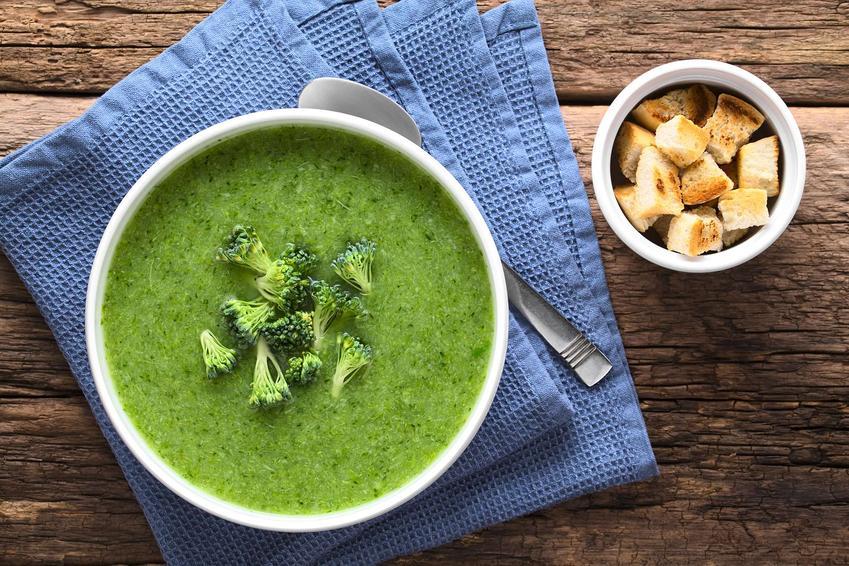 Zupa krem brokułowa podana w eleganckiej miseczce i udekorowana różyczkami brokułu.