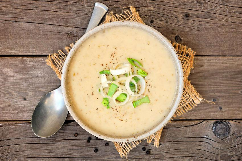 Zupa cebulowa krem znajduje się w wysokiej misce. Ozdobiona jest drobno pokrojonym szczypiorem. Obok miski leży łyżka. Pod talerzem leży pomarańczowy materiał. Całość znajduje się na drewnianym stole.