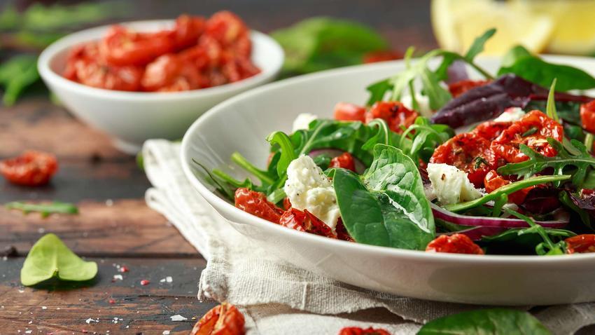 Sałatka ze szpinakiem i suszonymi pomidorami udekorowana serem feta.