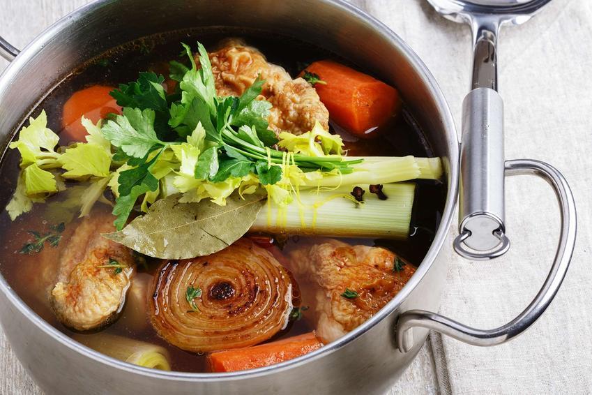 Rosół z indyka w garnku z warzywami, udekorowany gałązką pietruszki.