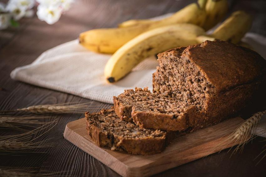 Ciasto bananowe znajduje się na drewnianej deseczce. Obok leżą banany oraz kłosy pszenicy.