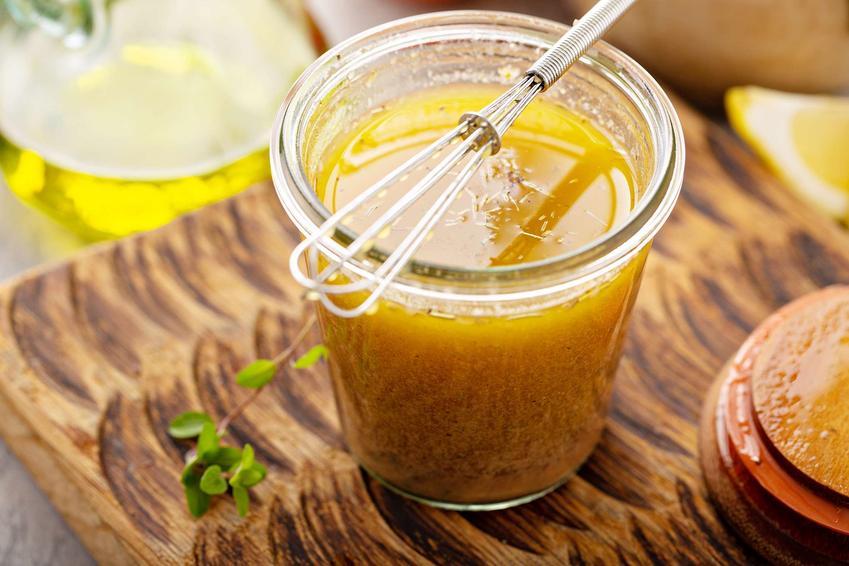 Sos do sałatki greckiej podany w słoiczku, na nim rózga do mieszania, na desce do krojenia, w tle cytryna i oliwa.