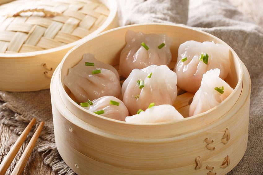 Tradycyjne, chińskie pierożki gotowane na parze podane w okrągłych bambusowych naczyniach, posypane szczypiorkiem.