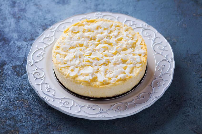 Sernik z mlekiem kokosowym znajduje się na dekoracyjnym, białym talerzu. Przyozdobiony jest wiórkami kokosa. Talerz stoi na ciemnym blacie.