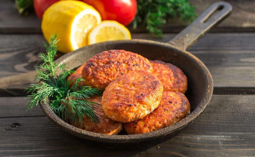 Kotlety rybne znajdują się w żeliwnej patelni. Obok leżą cytryny oraz pomidory.