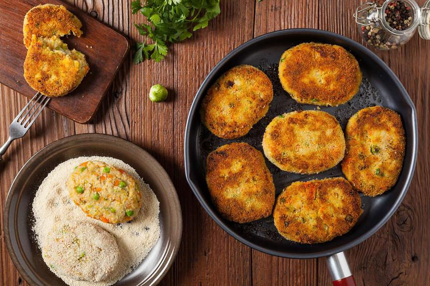 Kotlety warzywne znajdują się na patelni, na desce i na talerzu z bułką tartą.